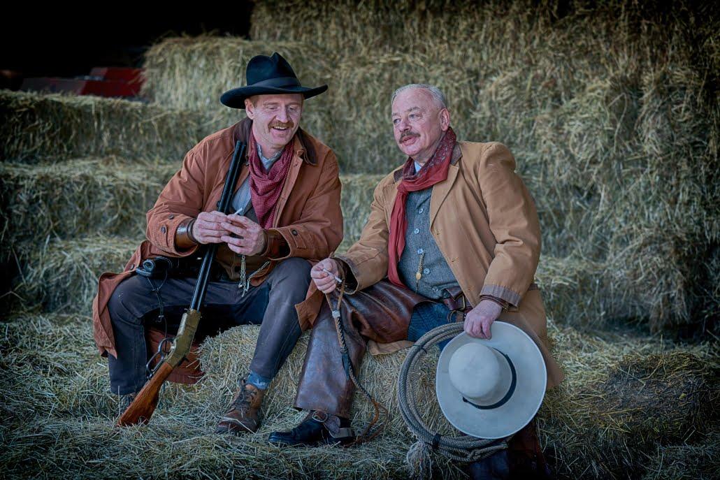 two men (cowboys) in brown coat sitting on hay stack