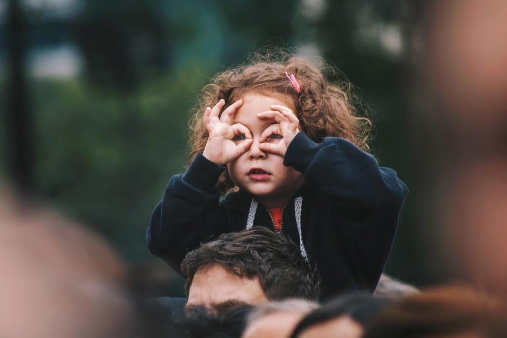 girl making hand gesture like binoculars on her face